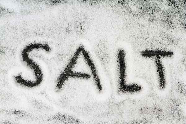 the word salt written in salt by tracing the letters in the crystals on a black background